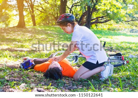 First Aid Emergency CPR. After Bicycle Race A Cyclist man has Heart Attack or Shock. A woman  give CPR for first aid Cyclist man. Emergency , safe life , Photo concept Heart Attack and CPR.  #1150122641