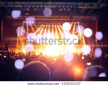 Concert fans silhouette in front of an illuminated stage #1150155137
