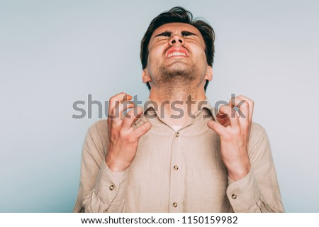 infuriated rage and anger. man went berserk with fury. portrait of a young brunet guy on light background. emotion facial expression. feelings and people reaction concept. Royalty-Free Stock Photo #1150159982