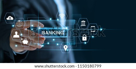 Businessman holding word banking in hand with icon network connection on virtual screen dark background Royalty-Free Stock Photo #1150180799