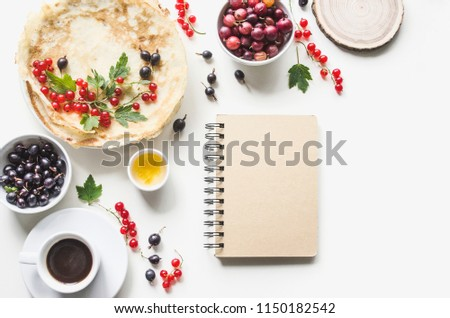 Breakfast from homemade pancakes and coffee with fresh berries of currants and gooseberries. With notepad recipe.  Flat lay, top view, copy space,  mock-up