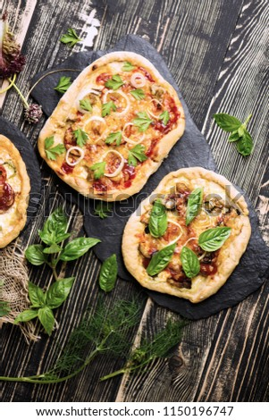 Italian pizza and pizza ingredients served on wooden background. Pizza margarita with tomatoes, olive, basil and mozzarella close up. #1150196747