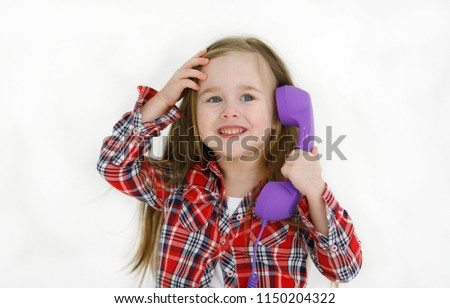Emotional portrait of a cheerful and positive little beautiful girl with flowing hair looking up with a smile up while talking on the phone with mom and holding the phone in her hand . Childhood #1150204322
