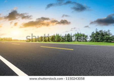 Empty asphalt road and green forest landscape at sunrise #1150243058
