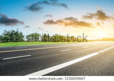 Empty asphalt road and green forest landscape at sunrise #1150243067