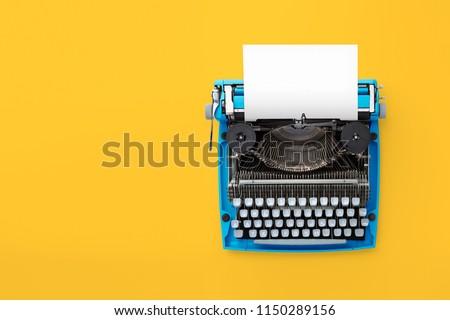 Typewriter machine in retro style on yellow background. Top view. #1150289156
