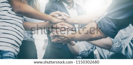 Close up view of young business people putting their hands together. Stack of hands. Unity and teamwork concept. #1150302680