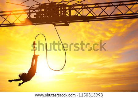 Silhouette of women jumping down bungee jump sport in sunset and light flare #1150313993