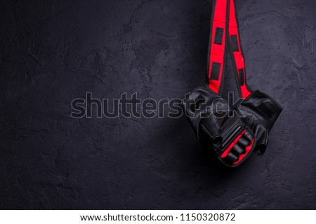 Gloves for MMA hang on nail on a black texture wall.  Royalty-Free Stock Photo #1150320872