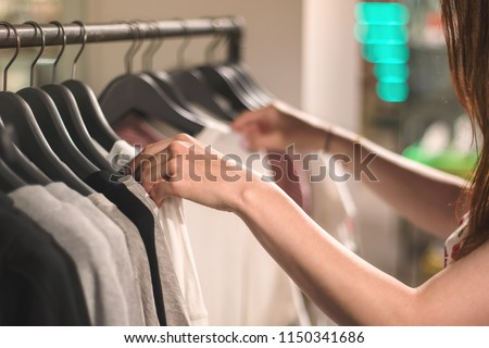 A young woman chooses clothes on hangers in the shop, store, boutique, showroom or shopping mall. Pastel colors. Close up with blurred background #1150341686