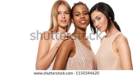 Portrait of beautiful multiracial young women with different  skin. Happy african-american young woman in centre with asian and caucasian girls on side. Isolated on white background #1150344620