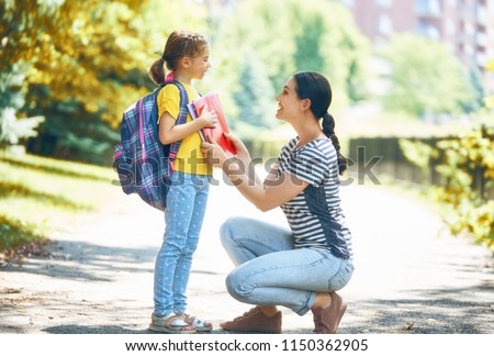 Parent and pupil of primary school go hand in hand. Woman and girl with backpack behind the back. Beginning of lessons. First day of fall. #1150362905