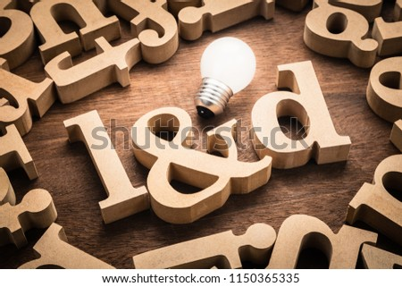 L&D (Learning and Development) wood letters with glowing light bulb among the scattered letters on the table #1150365335