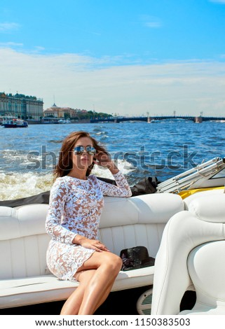 Portrait of a young brunette in sunglasses and a dress in a speedboat. #1150383503