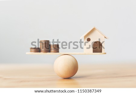 Wooden home and money coins stack on wood scale. Property investment and house mortgage financial real estate concept #1150387349