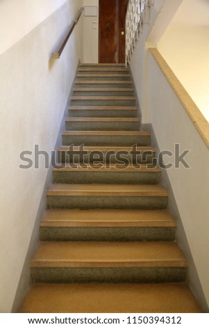 Old stone staircase with a handrail in a building without an elevator #1150394312