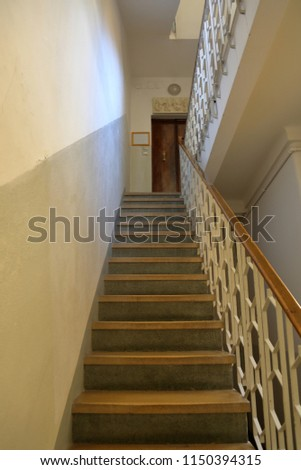 Old stone staircase with a handrail in a building without an elevator #1150394315