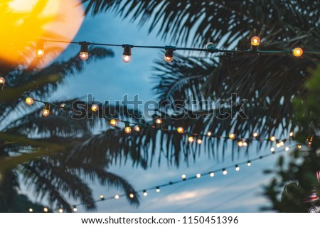 blurred light bokeh with coconut palm tree background on sunset, yellow string lights with bokeh decor in outdoor restaurant #1150451396