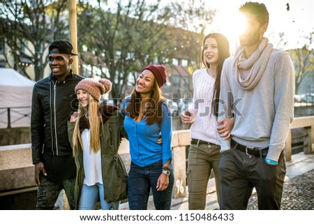 Group of multi-ethnic friends walking on the streets and smiling - Young people having fun outdoors #1150486433