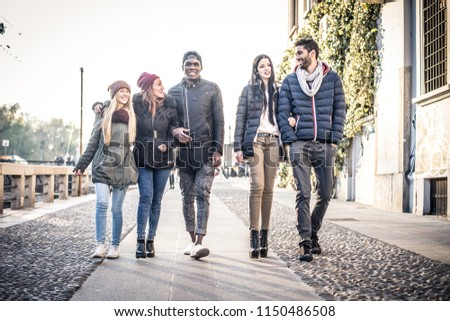 Group of multi-ethnic friends walking on the streets and smiling - Young people having fun outdoors #1150486508