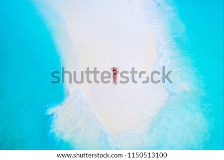 Beautiful woman tans on sandbank surrounded by turquoise ocean from above #1150513100