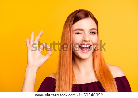 Funnyand joyful girl shows okay sign and winks looking at camera isolated on yellow background