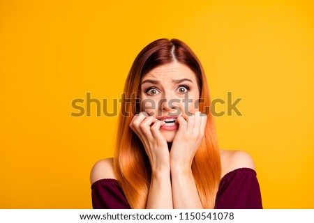 Portrait of red straight-haired attractive cute nice scared worried young girl, biting nails. Isolated over bright vivid yellow background #1150541078