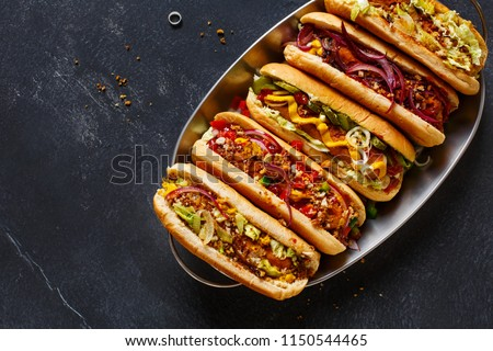 Hot dogs fully loaded with assorted toppings on a tray. Top view #1150544465