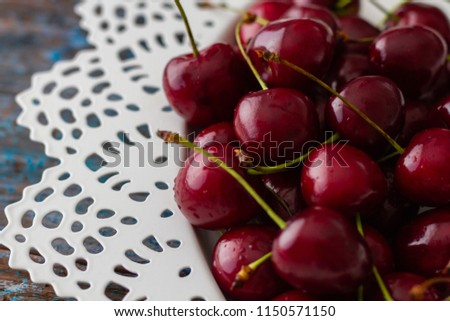 Fresh cherry berries in white bowl on rustic wooden table and vintage background #1150571150