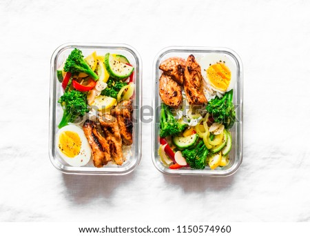Rice, stewed vegetables, egg, teriyaki chicken - healthy balanced lunch box on a light background, top view. Home food for office concept. Copy space   #1150574960