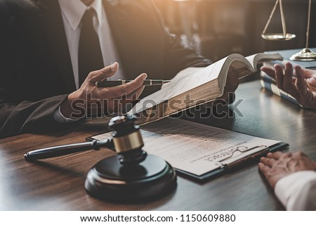 Judge gavel with Justice lawyers having team meeting at law firm background. Concepts of Law and Legal services. #1150609880
