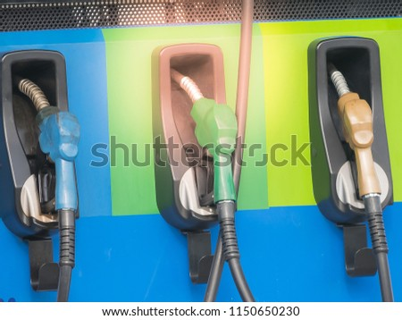 blue green orange fuel gasoline dispenser nozzles background at gas station #1150650230