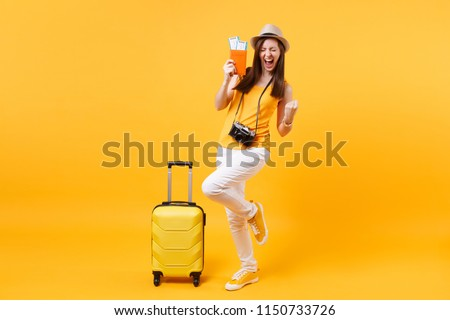 Excited happy tourist woman in summer hat with passport, ticket, suitcase, doing winner gesture isolated on yellow background. Female traveling abroad to travel weekends getaway. Air flight concept #1150733726