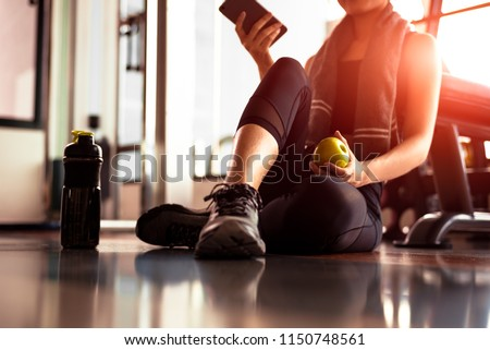 Close up of woman using smart phone and holding apple while workout in fitness gym. Sport and Technology concept. Lifestyles and Healthcare theme. #1150748561