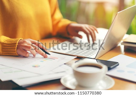 Young serious accountant woman checking paperwork from accounting department to analyse number on document, using laptop check business database, information comparing. Typing keyboard for recording #1150770380