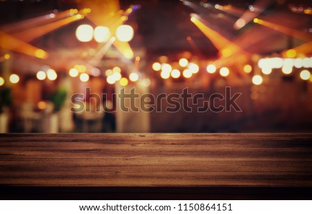 Image of wooden table in front of abstract blurred restaurant lights background #1150864151