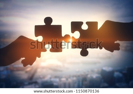 Puzzle piece silhouette on blurry city backdrop. Teamwork and jigsaw concept. Double exposure  #1150870136