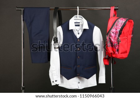Male classical suit on hanger and schoolbag on black background. Concept school uniform. #1150966043