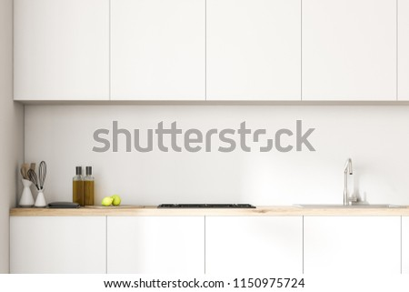 White kitchen counters with a cooker, kitchenware and bottles on them. A row of closets hanging above it in a white room. Close up. 3d rendering mock up #1150975724