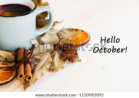 Autumn, fall leaves, hot steaming cup of glint wine on wooden table background. Seasonal, autumnal hot wine, Autumn relaxing and still life concept. Top view with text hello october.  #1150983092