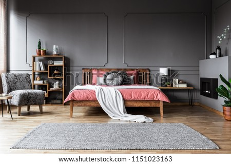 Carpet in spacious grey and pink bedroom interior with wooden bed and patterned armchair #1151023163
