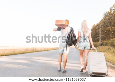 A loving couple walks along the road with a guitar and suitcases and catches a car hitchhiking. #1151059037