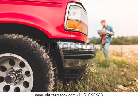 close-up shot of red truck standing in field with blurred man navigating with map on background #1151066663