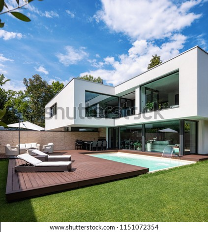 Exterior modern white villa with pool and garden, nobody inside #1151072354