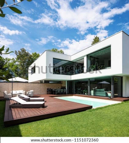 Exterior modern white villa with pool and garden, nobody inside #1151072360