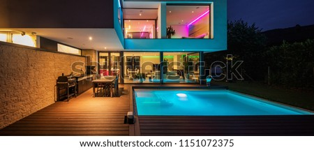 Modern villa with colored led lights at night. Nobody inside #1151072375