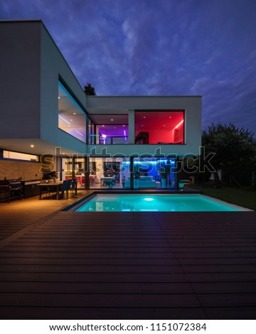 Modern villa with colored led lights at night. Nobody inside #1151072384