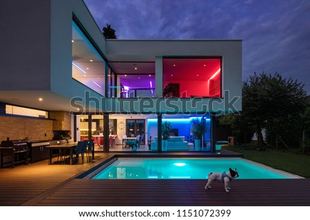 Modern villa with colored led lights at night. Nobody inside #1151072399