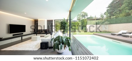 Modern living room overlooking the garden and swimming pool. Nobody inside #1151072402
