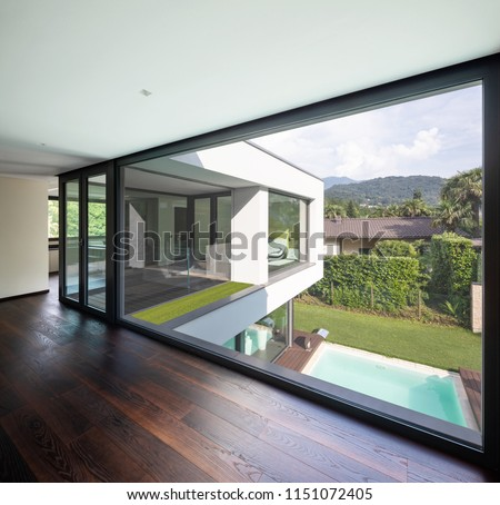 Large window in hallway of modern villa overlooking the private pool. Nobody inside #1151072405